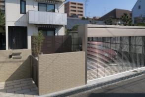 外構リフォーム -錆御影のアプローチとガレージとタイル門柱のエクステリア写真